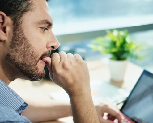 Anxious Businessman Biting Nails Working With Business Data Loss